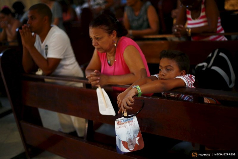Boy holds an image of  Pope Francis during a mass celebrating the pope's visit, in the church of the Virgin of Charity of El Cobre in Havana