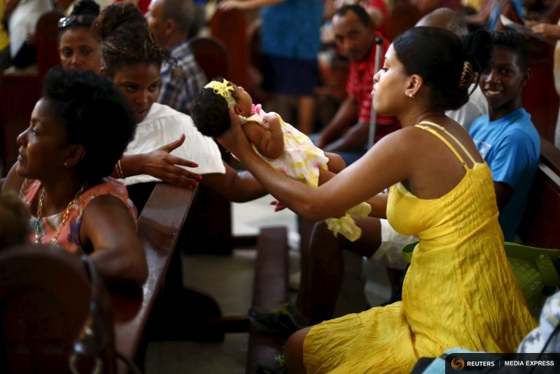 Parishioner holds a baby during a mass celebrating Pope Francis' visit, in the church of the Virgin of Charity of El Cobre in Havana