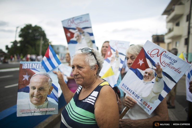 Teresa Fernandez Salgado holds a sign with an image of Pope Francis as she waits for his arrival from the airport in Havana
