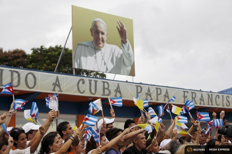 People react after the arrival of Pope Francis outside the airport in Havana