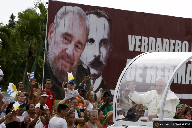 Pope Francis greets believers while he passes in front of a billboard with and image of Cuba's former leader Fidel Castro and Cuban independence hero Jose Marti, outside the airport in Havana