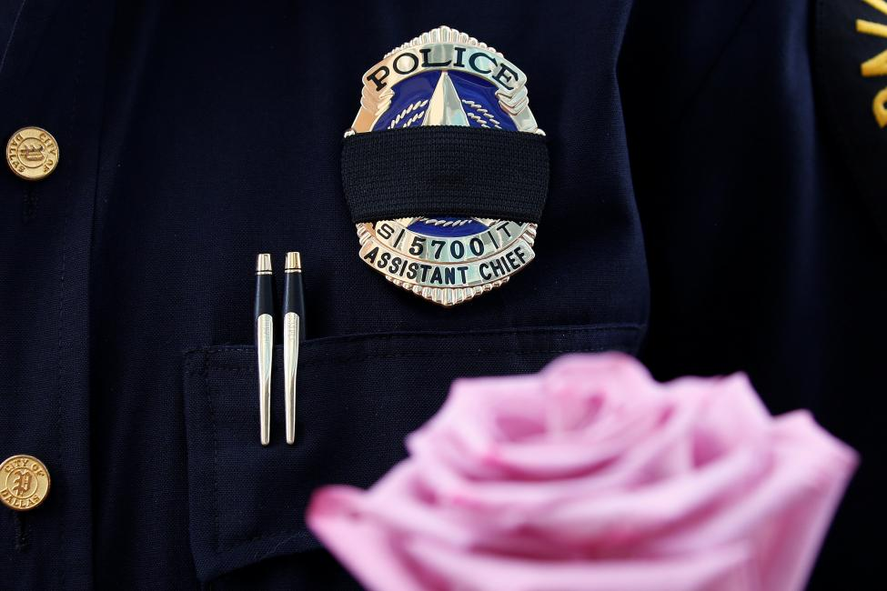 A Dallas Police wears a mourning band as he pays respects at a makeshift memorial at Dallas Police Headquarters following the multiple police shootings in Dallas
