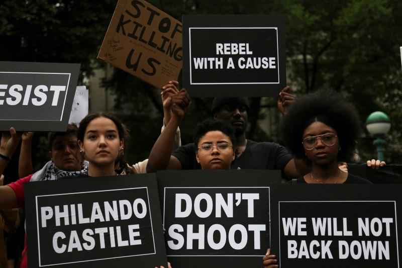 Protesters hold signs ahead of a march against police brutality in Manhattan, New York