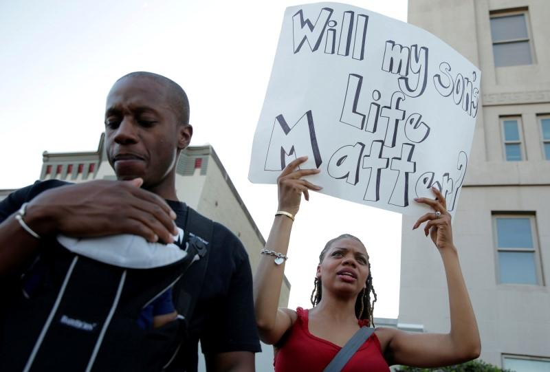 Alex Brown carries his two-month-old son Noah as his wife Lakeisha carries a sign during a Black Lives Matter protest in Washington