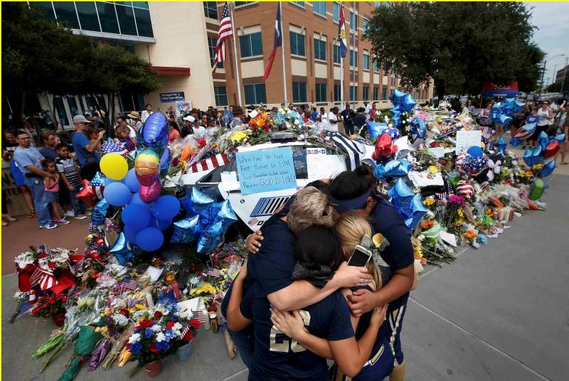 A softball team hugs after paying their respects at a makeshift memorial at Dallas Police Headquarters following the multiple police shootings in Dallas,