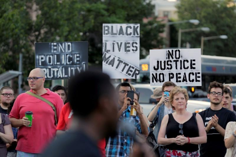 Demonstrators with Black Lives Matter hold up signs before a protest march in Washington