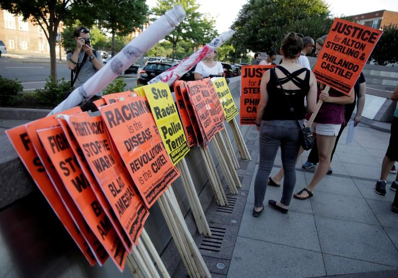 Demonstrators with Black Lives Matter gather signs before a protest march in Washington