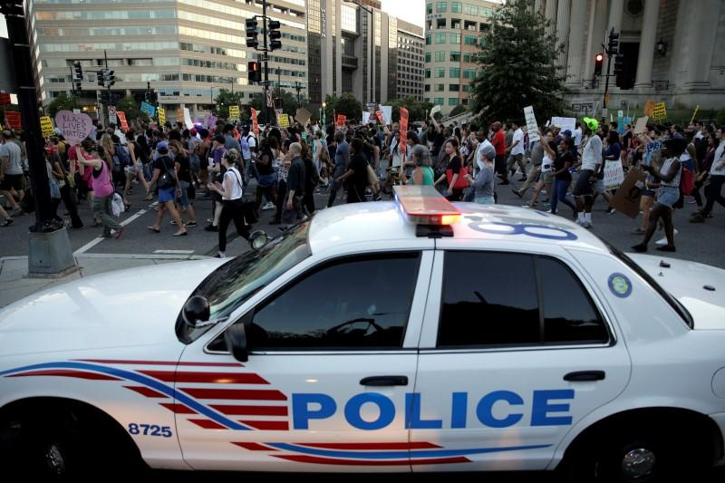 Demonstrators with Black Lives Matter march past a Metropolitan police officer blocking traffic during a protest in Washington