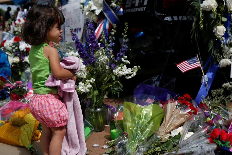 Abigail Garcia,2, visits a makeshift memorial at Dallas Police Headquarters two days after a lone gunman ambushed and killed five police officers at a protest decrying police shootings of black men, in Dallas, Texas