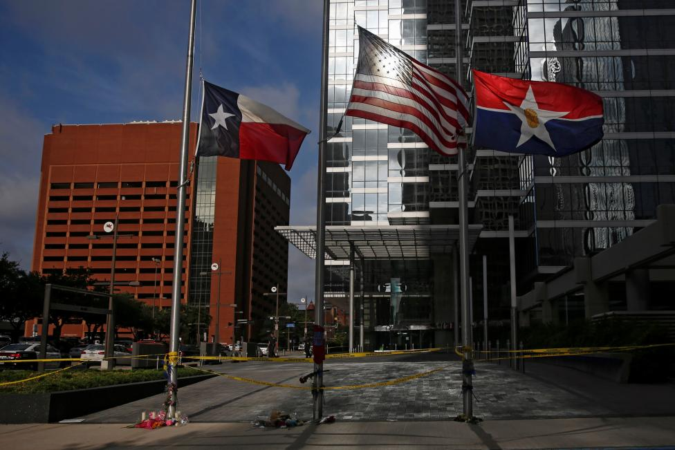 Flags fly at half mast at makeshift memorial near the crime scene two days after a lone gunman ambushed and killed five police officers at a protest decrying police shootings of black men, in Dallas
