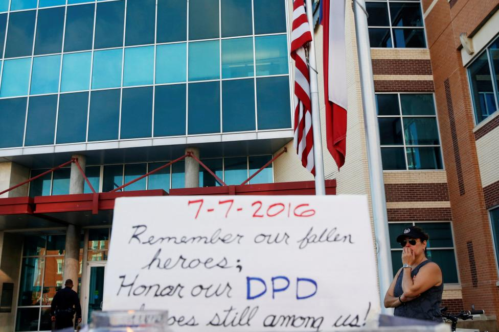 A woman stands by a makeshift memorial at Dallas Police Headquarters two days after a lone gunman ambushed and killed five police officers at a protest decrying police shootings of black men, in Dallas, Texas