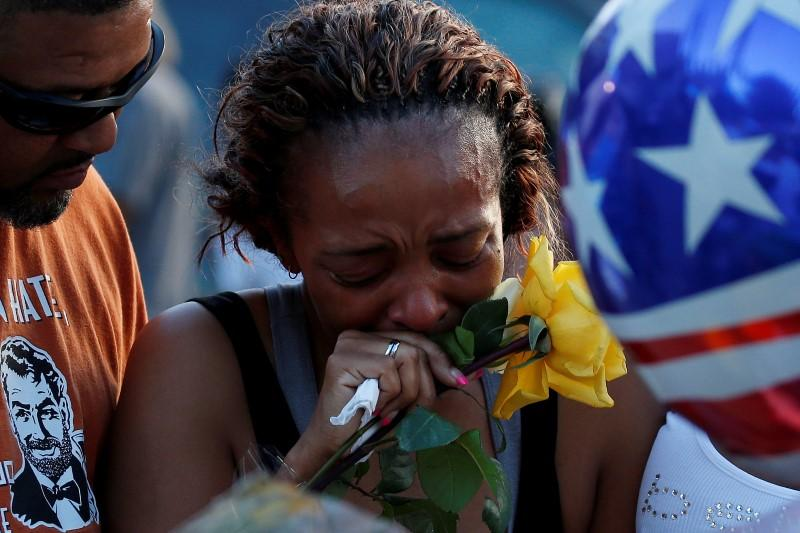 Victor Taylor supports Keaka Wallace, who says she was a patrol partner of slain DART officer Brent Thompson, weeps as she leaves a makeshift memorial at Dallas Police Headquarters following the multiple police shooting in Dallas