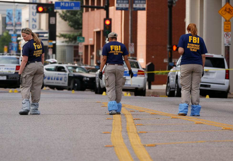 Members of the FBI Evidence Response Team survey the crime scene two days after a lone gunman ambushed and killed five police officers at a protest decrying police shootings of black men, in Dallas, Texas