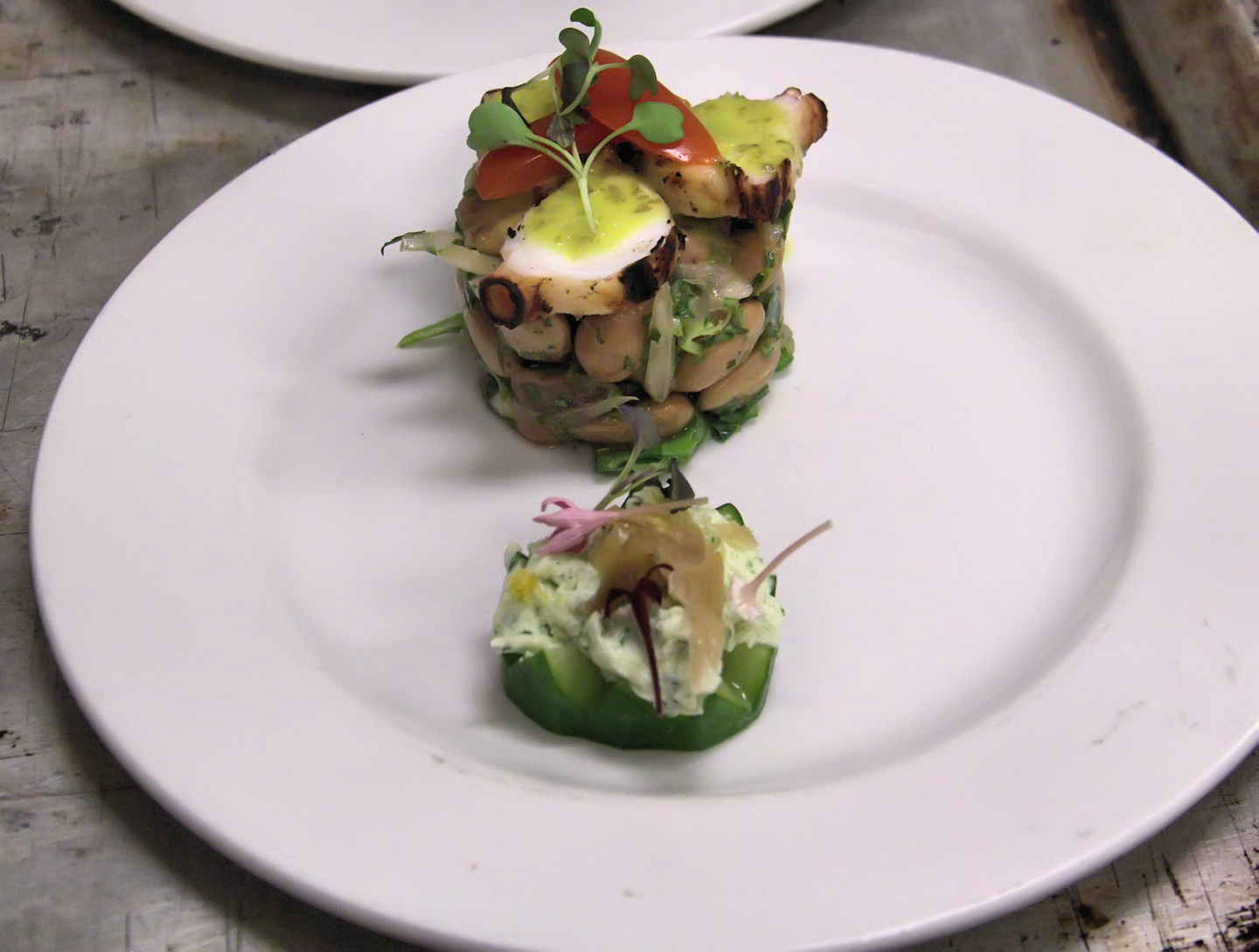 Cucumber canape and grilled octopus cranberry bean tower