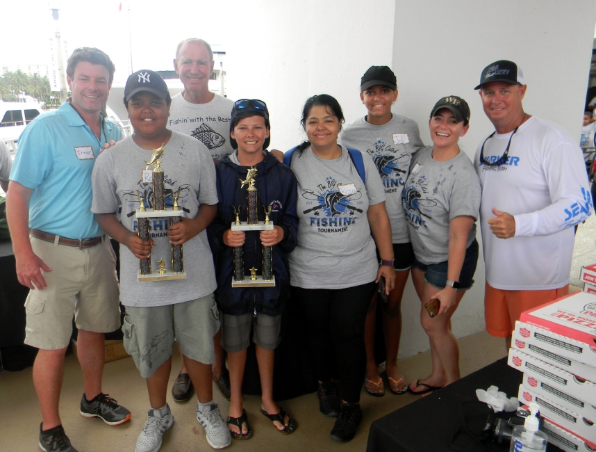 Little Brother Ray and young tournament participant Trey show off their first place trophies for catching the largest fish.  They are pictured with event chairs Trevor Carroll and John Weller (back) Ray's mother, Rosa, Little Sister Joli with her Big Sister Lindsay Johns and Captain Grey Marker of Markerita..