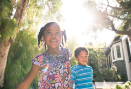 African American girl and boy hold hands and walk during a sunny day.