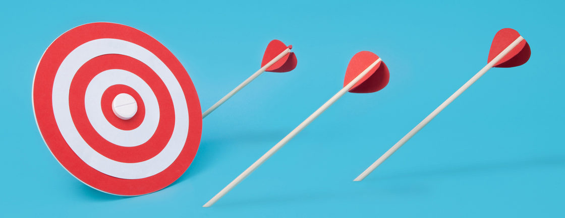 Several arrows have fallen short of their target, which is a pill on a bullseye. This image suggests that a drug targeted towards autism's symptoms has not yet been made.