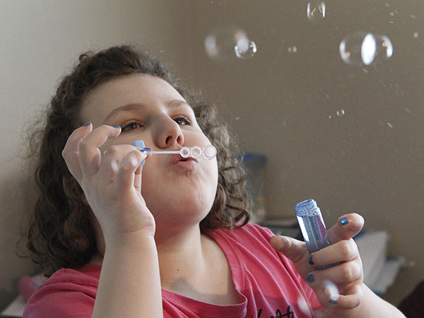 Clear interests: Alex Garish enjoys blowing bubbles in her family's living room when she gets home from school. Photos by Marie-France Coallier