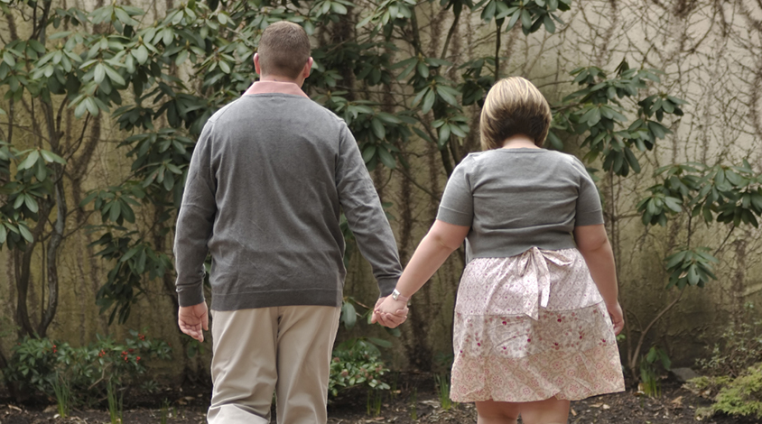 Man and woman walking hand-in-hand.