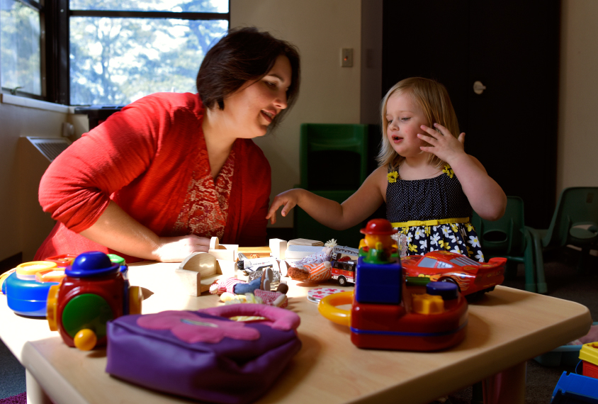 Mommy magic: Somer Bishop plays with her daughter Lila, 3, who does not have autism, at a table full of toys Bishop uses to evaluate children for autism.