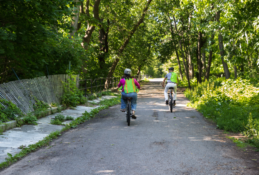 Photo: Gina and Bernardo ride bikes together, both wearing neon green visibility vests.
