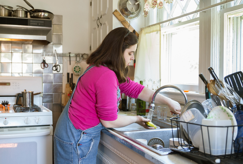 Photo: Gina Pace washes dishes at the sink. She has shoulder-length straight brown hair and is wearing a pink long-sleeved shirt under denim overalls.