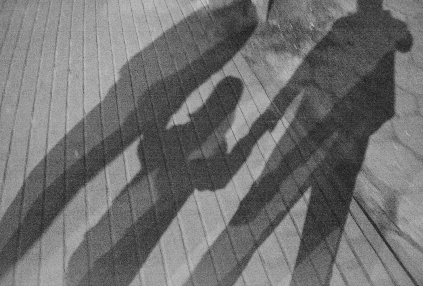 diagonal shadow of a family--parents and a girl