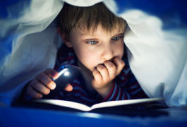 boy reading book under covers with flashlight