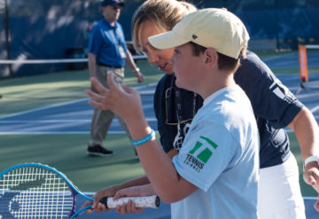 Boy holds tennis racket on court with teacher