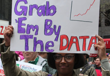 """Woman at a protest holds a sign that says """"Grab 'em by the data"""""""