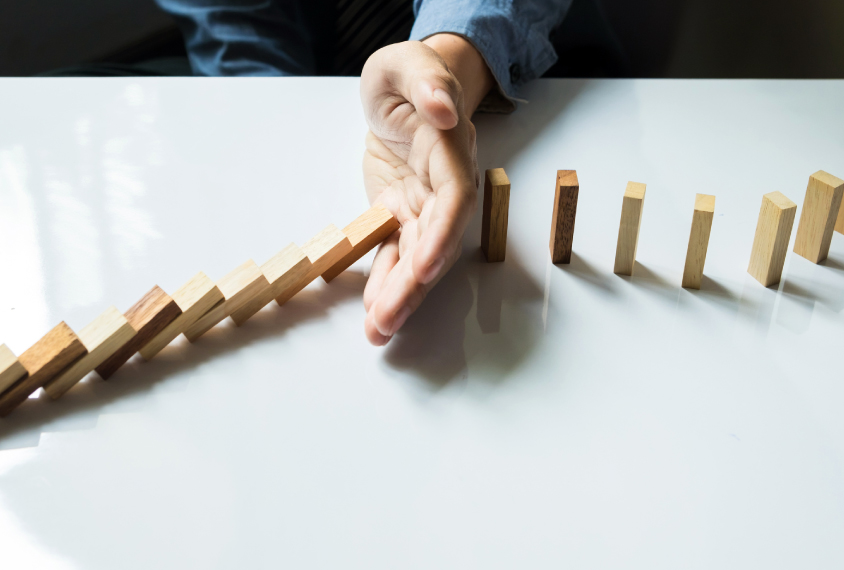 Hand stopping a row of dominoes from collapsing.