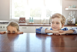 A young boy and a young girl hiding behind the kitchen table.