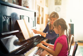 Girl playing the piano while a teacher guides her along the music.