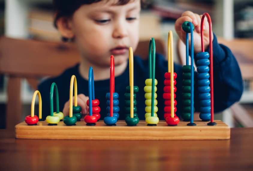 Toddler playing with stacking colorful beads on a toy.