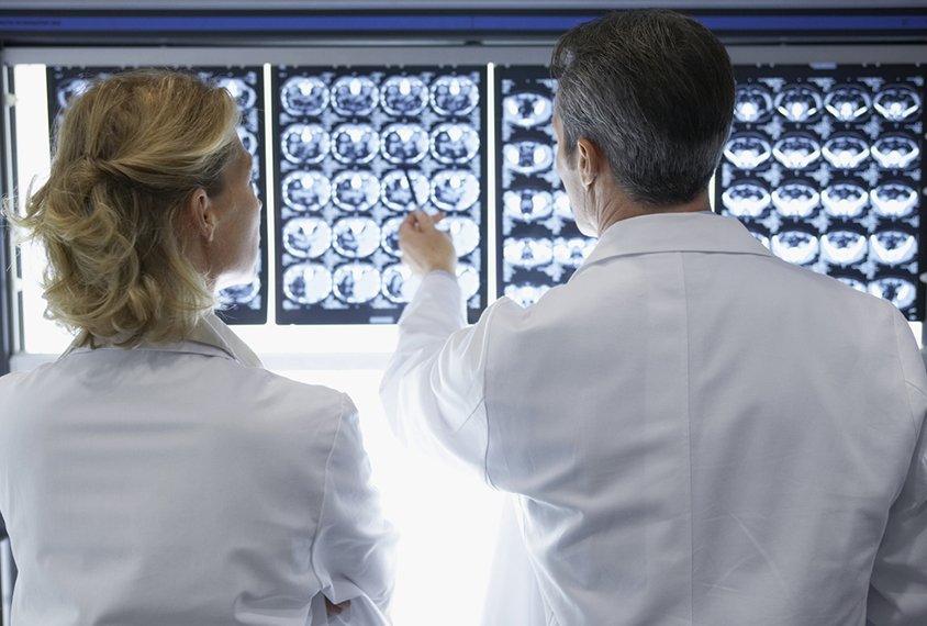 Two doctors reviewing brain scans.
