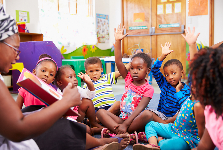 Children in pre-school sitting around a learning circle.