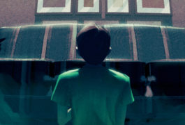 Boy standing gazing up at building anxiously.