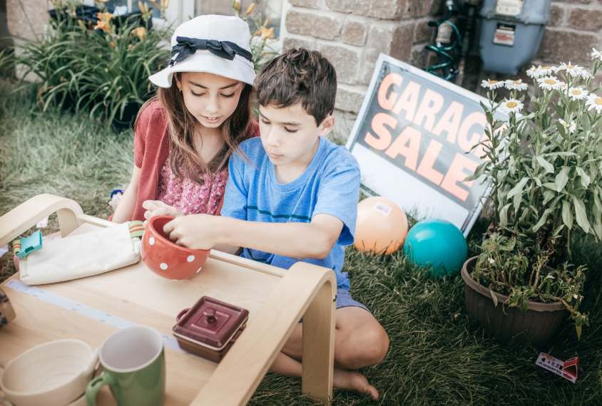 Two children sitting at a garage sale table.