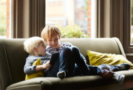 Boy and toddler sitting on sofa.