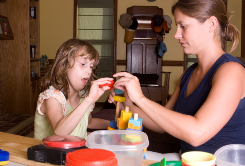 Woman and girl examining toy