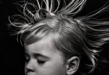 Toddler girl sleeping with hair floating against black background.