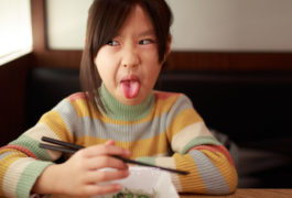 child sticking tongue out and making a face while holding chopsticks