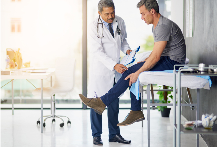 doctor touching male patient's knee