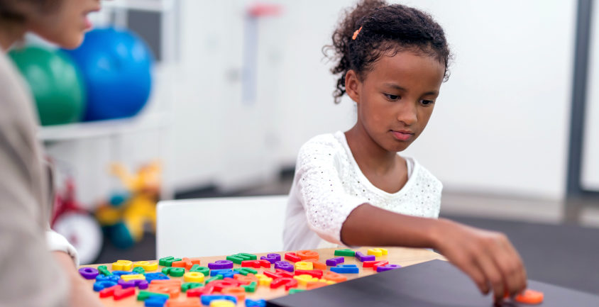 child playing with colorful puzzle