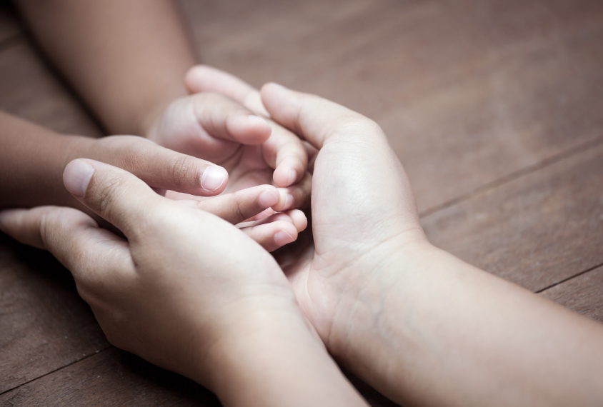 large adult hands holding small children's hands