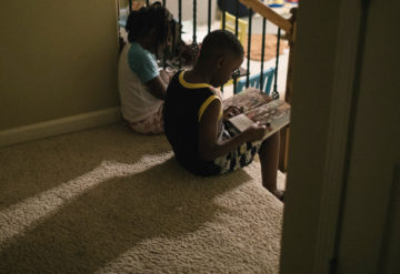 Photo: two children sit on the top step of a flight of carpeted stairs, reading size by side.