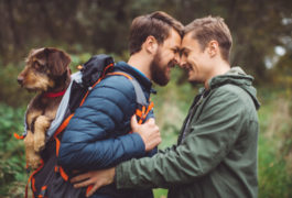 two men hiking and embracing with dog in backpack
