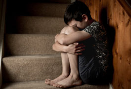 child anxiously sitting in stairwell holding knees closely