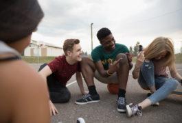 four teenage friends sitting outside in parking lot