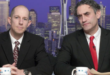 Two men dressed as news anchors look at the camera.